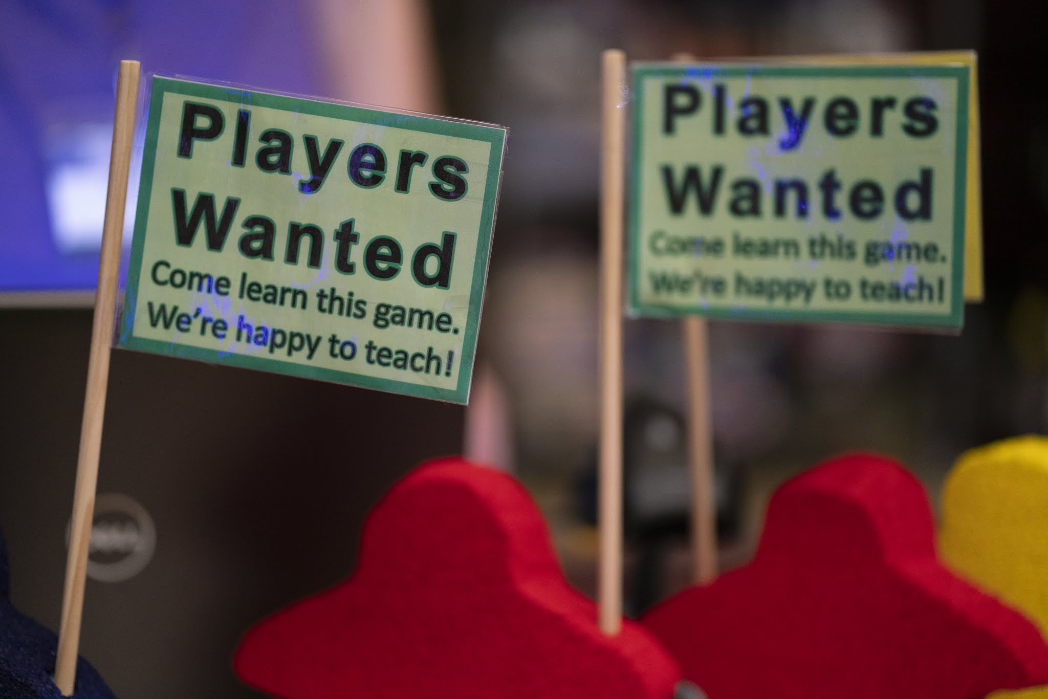 "Meeple-shaped sign holders. Sign Reads ""Players Wanted - Come Learn This Game. We're Happy to Teach!"""